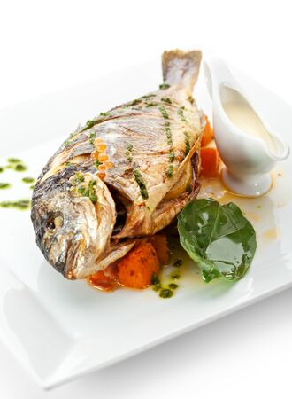 Fried Fish (Dorado) Garnished on Sliced Pumpkin with Basil Leaf and Sauce Stock Photo - 15173007