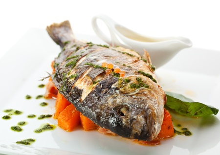 Fried Fish (Dorado) Garnished on Sliced Pumpkin with Basil Leaf and Sauce Stock Photo - 15159854