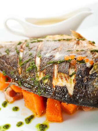 Fried Fish (Dorado) Garnished on Sliced Pumpkin with Basil Leaf and Sauce Stock Photo - 15173390