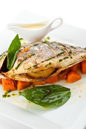 Fried Fish (Dorado) Garnished on Sliced Pumpkin with Basil Leaf and Sauce photo