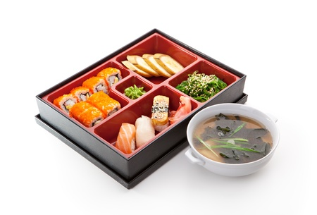 Japanese Meal in a Box (Bento) - Nigiri Sushi, Maki Sushi, Chuka Salad and Banana. Garnished with Miso Soup photo