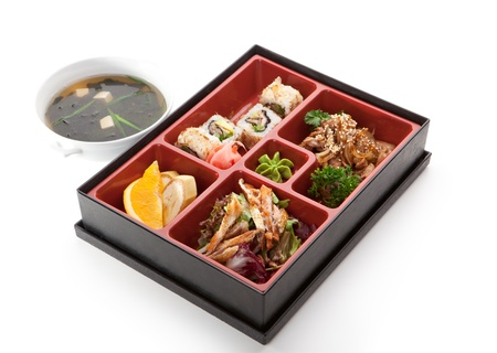 bento: Japanese Meal in a Box (Bento) - Salad, Meat Cuts and Sushi Roll, Orange and Banana. Garnished with Miso Soup