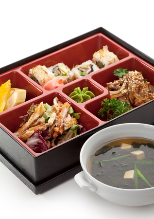 Japanese Meal in a Box (Bento) - Salad, Meat Cuts and Sushi Roll, Orange and Banana. Garnished with Miso Soup photo