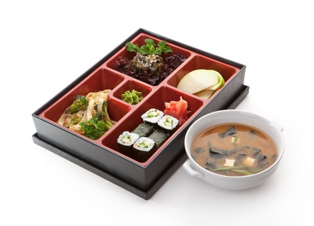 Japanese Meal in a Box (Bento) - Salad, Noodles and Cucumber Sushi Roll, Apple Slice photo