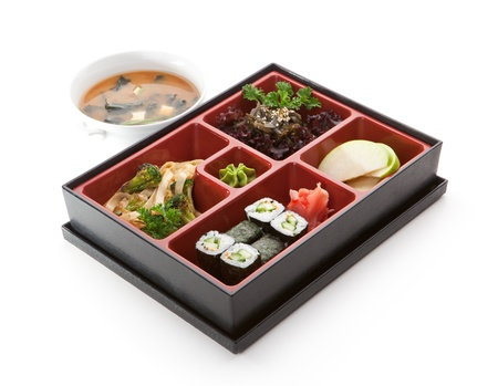 bento: Japanese Meal in a Box (Bento) - Salad, Noodles and Cucumber Sushi Roll, Apple Slice Stock Photo
