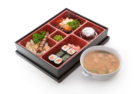 bento: Japanese Meal in a Box (Bento) - Salad, Skewered Meat with Rice, Salmon Sushi Roll and Dessert. Garnished with Miso Soup