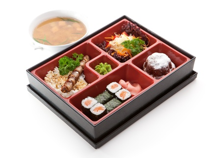 Japanese Meal in a Box (Bento) - Salad, Skewered Meat with Rice, Salmon Sushi Roll and Dessert. Garnished with Miso Soup photo