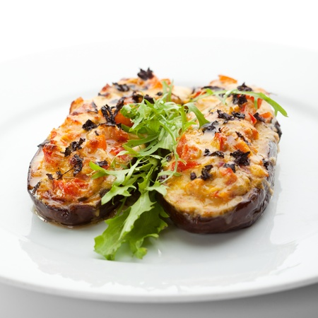black dish: Baked Eggplant with Vegetables. Garnished with Fresh Greens Stock Photo
