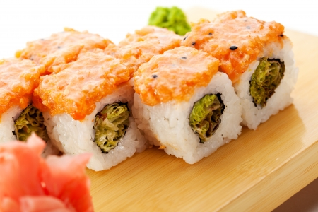 sake maki: Maki Sushi - Roll with Green Lettuce inside. Topped with Sliced Salmon