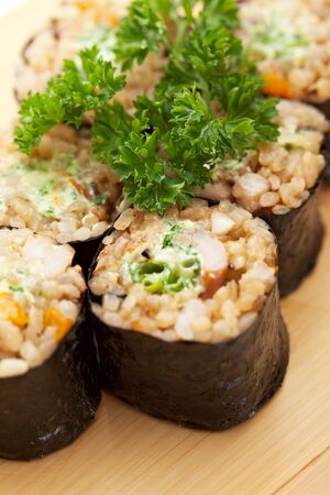 brown rice: Maki Sushi - Roll with Brown Rice and Green Lettuce inside. Garnished with Ginger and Wasabi Stock Photo