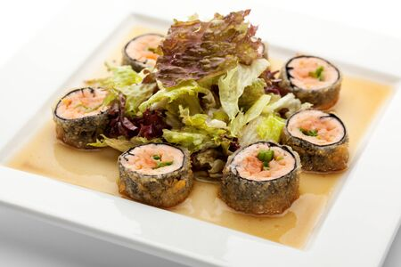 sake maki: Japanese Cuisine - Deep-fried Sushi Roll with Salmon and Lettuce inside. Served with Salad Leaf and Sauce