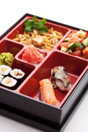 bento box: Japanese Meal in a Box (Bento) - Salad, Noodles, Sushi Roll, Nigiri Sushi Stock Photo