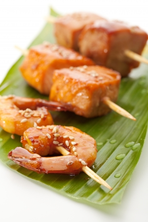 prawn skewers: Grilled Shrimps, Salmon and Chicken Meat  Garnished on Green Banana Leaf Stock Photo