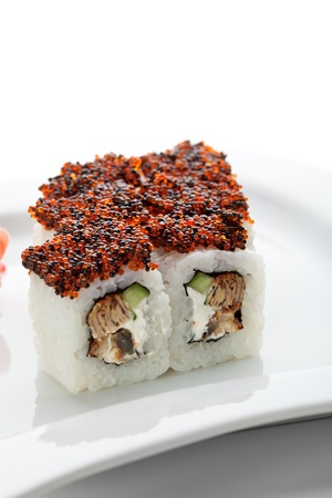 philadelphia roll: Maki Sushi - Roll made of Cream Cheese, Tamago (japanese omelet), Cucumber and Smoked Eel inside. Topped with Red and Black Tobiko (flying fish roe) Stock Photo