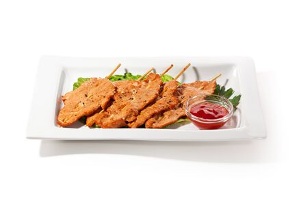 Chinese Cuisine - Skewered Pork on Salad Leaf with Spicy Sauce photo