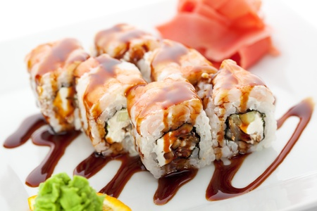 grig: Japanese Cuisine - Sushi Roll with Cucumber, Cream Cheese and Smoked Eel inside. Topped with Shrimp. Garnished with Unagi Sauce Stock Photo