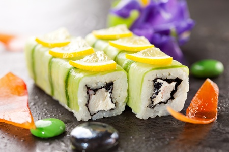 Cucumber Maki Sushi  - Roll made of Crab Meat, Cream Cheese and Black Tobiko (flying fish roe) inside. Cucumber outside. Topped with Lemon Slice photo