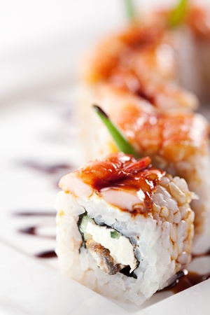 sushi roll: Japanese Cuisine - Sushi Roll with Cucumber, Cream Cheese and Smoked Eel inside. Topped with Shrimp. Garnished with Unagi Sauce Stock Photo