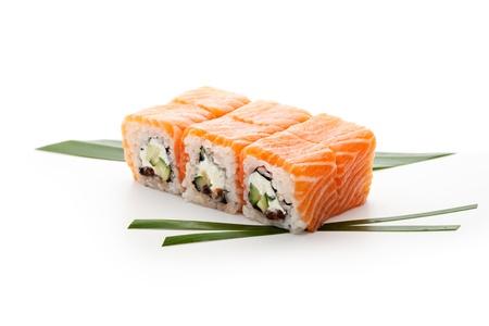 japanese sake: Rollo de Queso Crema, Huevas de salmón (ikura) y pepino dentro. El salmón y el exterior. Sirvió en la hoja Ensalada Foto de archivo
