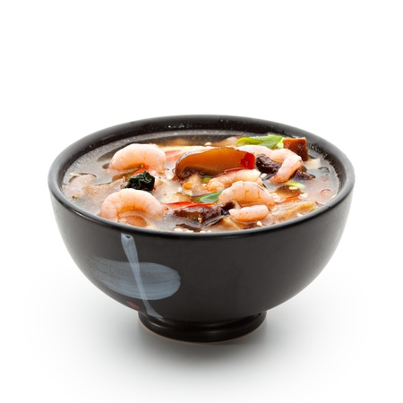 Japanese Cuisine - Suimono Soup made of Fish, Pork, Mushrooms, Shrimps and Noodles (Udon). Garnished with Pepper, Spring Onions and Sesame photo