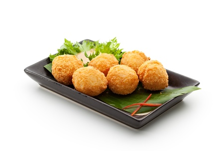 balls deep: Deep Fried Rice Balls with Salmon and Cream Cheese. Garnished on Green Leaf with Nuts Sauce