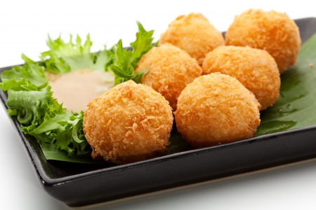 Deep Fried Rice Balls with Salmon and Cream Cheese. Garnished on Green Leaf with Nuts Sauce photo