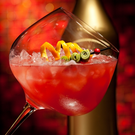 Red Cocktail with Vodka, Orange Juice, Berries and Liquor photo