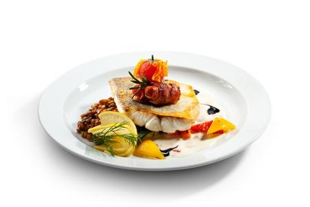 zander: Fried Fish (Zander) with Bacon. Garnished with Lemon,  Lentil and Vegetables