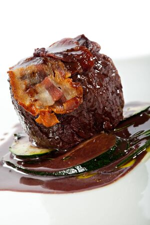 wine sauce: Fillet of Beef with Zucchini and Wine Sauce. Topped with Bacon Stock Photo