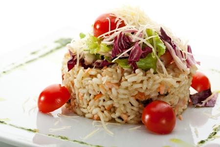 Risotto mit Lachs, Garnelen und Kirschtomaten. Garniert mit Salat Blätter