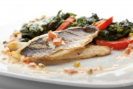 cooked fish: Fillet of Seabass with Tomato and Mussels Sauce. Garnished with Spinach and Tomato Stock Photo