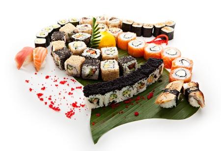 comida japonesa: Set de sushi - diferentes tipos de Maki Sushi y Nigiri Sushi. Sirvió en hojas verdes Foto de archivo