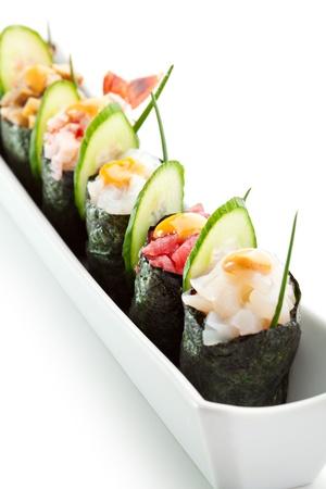 maki: Spicy Gunkan Sushi - Salmon, Omelette, Shrimp, Squid, Tuna and Scallop. Garnished with Cucumber