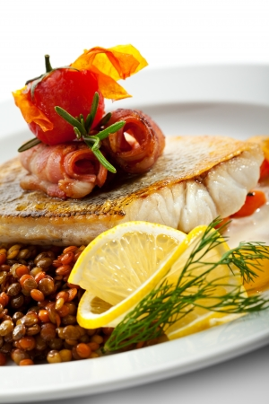 Fried Fish (Zander) with Bacon. Garnished with Lemon,  Lentil and Vegetables photo