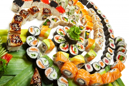 japanese culture: Sushi Set - Different Types of Maki Sushi and Nigiri Sushi. Served on Green Leaves