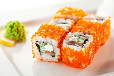 Maki Sushi with Fresh Salmon, Cucumber and Cream Cheese inside. Tobiko outside photo
