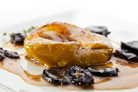 baked meat: Baked Apple with Foie Gras. Garnished with Prunes and Sauce