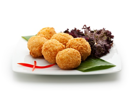 balls deep: Deep Fried Rice Croquette with Salmon and Cream Cheese. Garnished on Green Leaf with Sauce Stock Photo