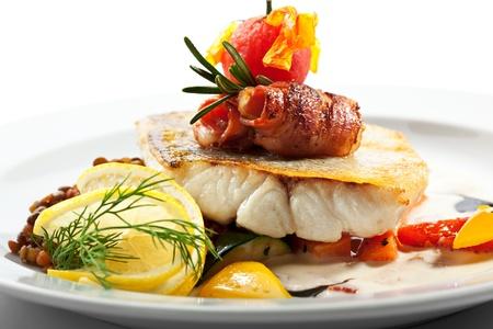 ベーコンと白身魚 (パイク)。レモン、レンズ豆、野菜を添えてください。