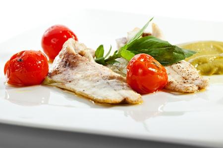 seabass: Filete de lubina al horno con tomate cherry, calabac?n y albahaca salsa de crema Foto de archivo