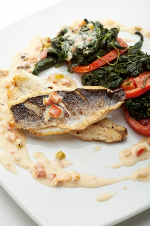 sea bass: Fillet of Seabass with Tomato and Mussels Sauce. Garnished with Spinach and Tomato Stock Photo