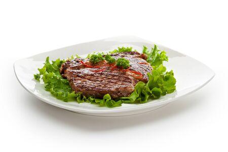 Grilled Foods - Steak on Fresh Salad Leaf photo