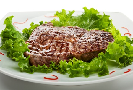 Grilled Foods - Steak on Fresh Salad Leaf photo