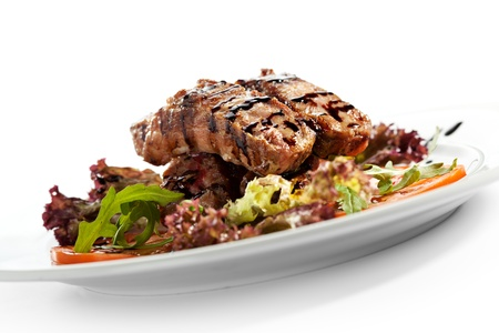 Hot Meat Dishes - Pork Ribs with Tomatoes and Fresh Salad Leaf photo