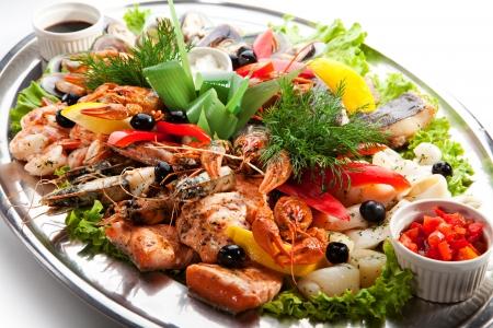 Seafood - Garnalen, inktvis, schelpen, mosselen, Zalmfilet, langoesten, Groenen en Lemon Stockfoto