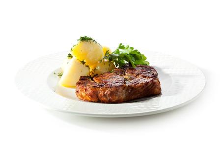 Schweinesteak mit Kartoffeln und Petersilie Standard-Bild - 25043725