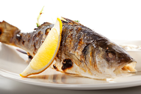 Grilled Foods - BBQ Sea Bass Fish with Lemon and Mixed Salad Stock Photo