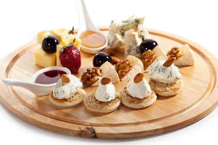 Cheese Plate with Grapes, Nuts, Honey and Berries Sauce photo