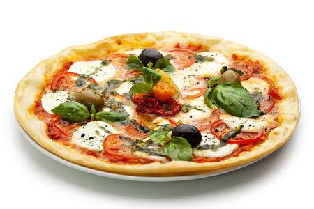 Pizza mit Mozzarella und frischen Tomaten und Pesto. Garniert mit getrockneten Tomaten, grünen und schwarzen Oliven und Basilikum