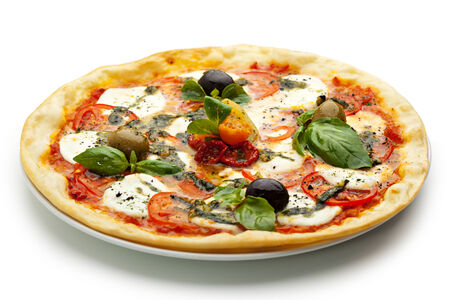 pizza pie: Pizza with Mozzarella Cheese and Fresh Tomato and Pesto Sauce. Garnished with Dried Tomato, Green and Black Olives and Basil Leaves Stock Photo
